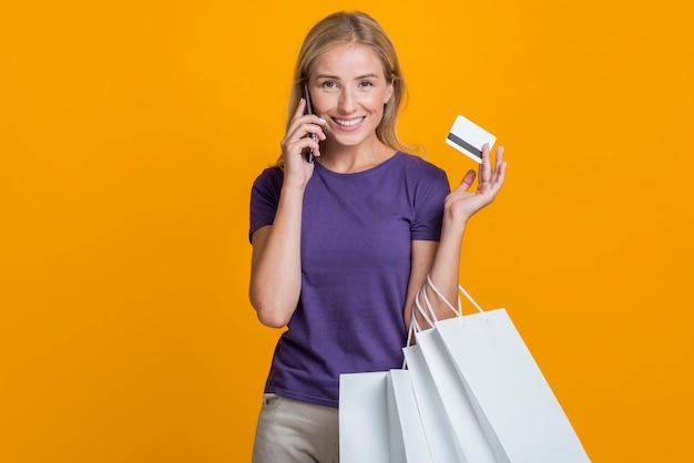 Vista frontal de uma mulher sorridente falando ao telefone e segurando um cartão de crédito e sacolas de compras