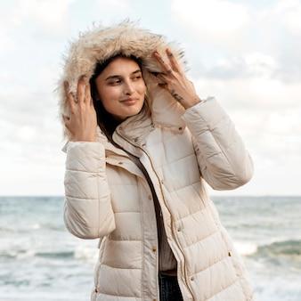 Vista frontal de uma mulher sorridente na praia com jaqueta de inverno