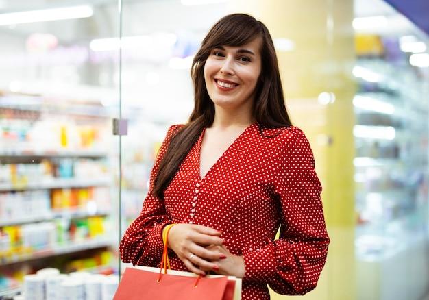 Vista frontal de uma mulher sorridente no shopping com sacolas de compras