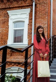 Vista frontal de uma mulher sorridente posando ao ar livre com sacolas de compras