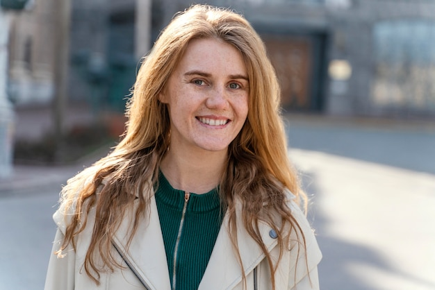 Vista frontal de uma mulher sorridente posando ao ar livre na cidade