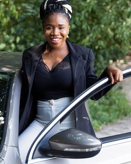 Vista frontal de uma mulher sorridente posando com a porta do carro aberta