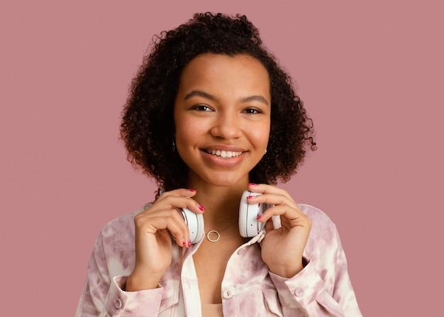 Vista frontal de uma mulher sorridente posando com fones de ouvido