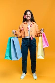 Vista frontal de uma mulher sorridente posando com sacolas de compras e etiquetas