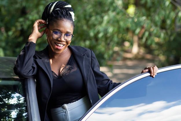 Vista frontal de uma mulher sorridente posando com seu carro novo