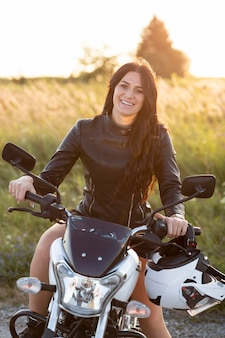 Vista frontal de uma mulher sorridente posando em sua motocicleta