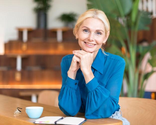 Vista frontal de uma mulher sorridente posando enquanto toma um café e trabalha