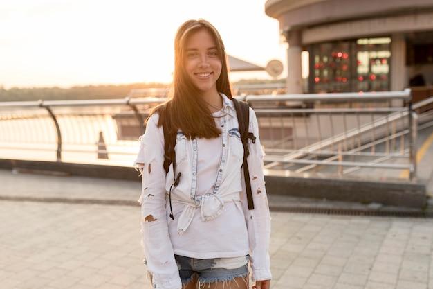Vista frontal de uma mulher sorridente posando enquanto viaja sozinha