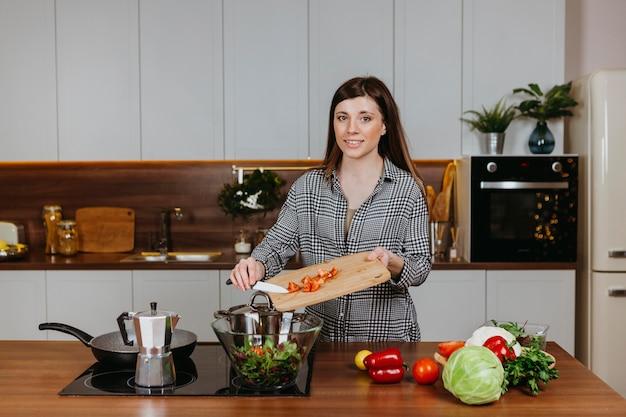 Vista frontal de uma mulher sorridente preparando comida na cozinha