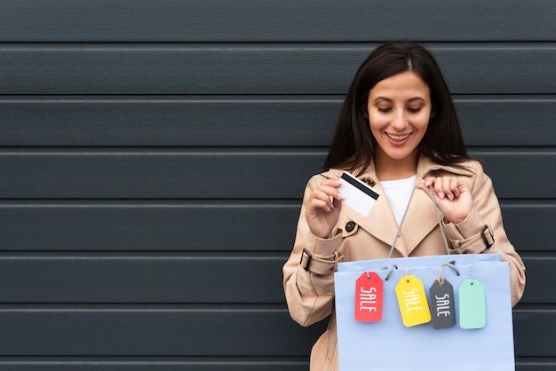Vista frontal de uma mulher sorridente segurando sacolas de compras com etiquetas e espaço de cópia