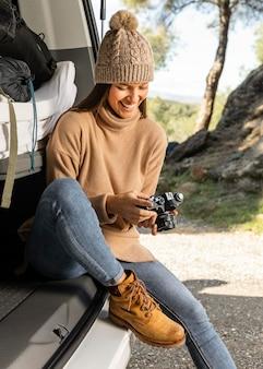 Vista frontal de uma mulher sorridente sentada no porta-malas do carro durante uma viagem e segurando a câmera