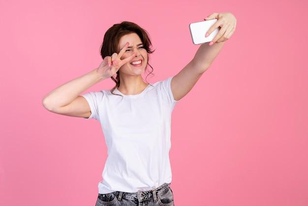 Vista frontal de uma mulher sorridente tirando uma selfie e fazendo o sinal da paz