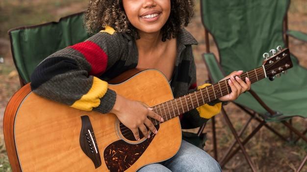 Vista frontal de uma mulher sorridente tocando violão enquanto acampa ao ar livre