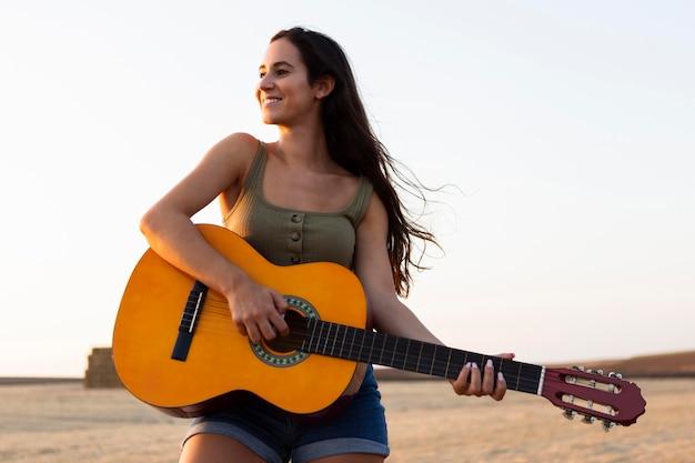 Vista frontal de uma mulher sorridente tocando violão na natureza