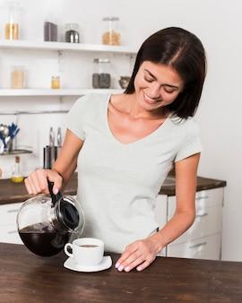Vista frontal de uma mulher sorridente tomando café em casa