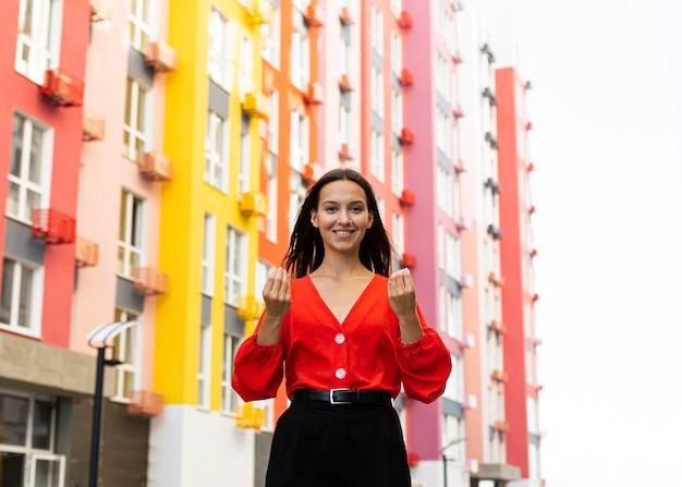 Vista frontal de uma mulher sorridente usando linguagem de sinais