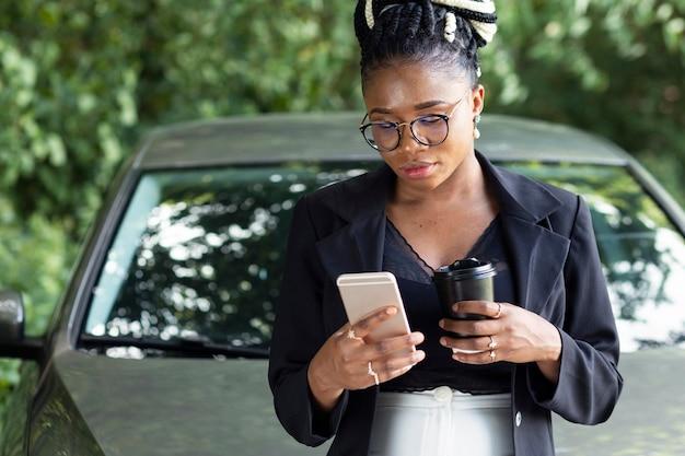 Vista frontal de uma mulher tomando café e olhando para o smartphone enquanto se encosta em seu carro