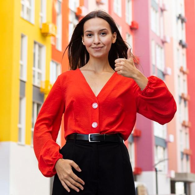 Vista frontal de uma mulher usando linguagem de sinais do lado de fora