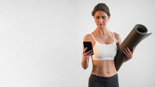 Vista frontal de uma mulher usando smartphone enquanto segura o tapete de ioga com espaço de cópia