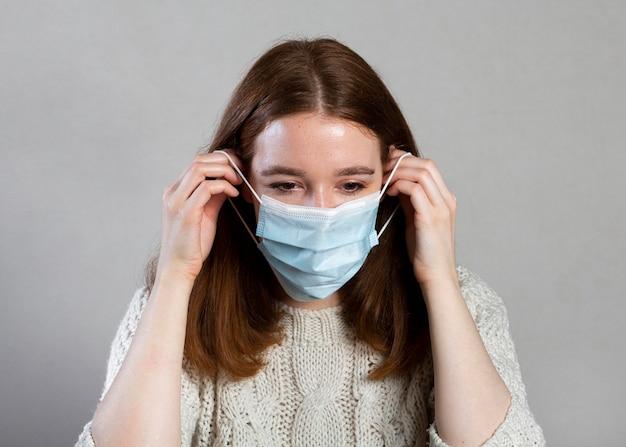 Vista frontal de uma mulher usando uma máscara médica para proteção