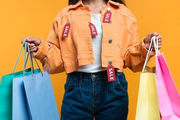 Vista frontal de uma mulher vestindo uma jaqueta com etiquetas e segurando sacolas de compras