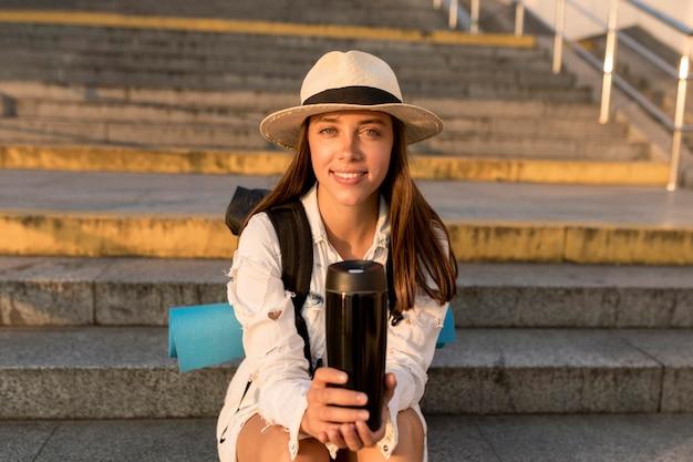 Vista frontal de uma mulher viajando com chapéu e mochila segurando uma garrafa térmica