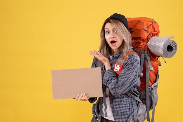 Vista frontal de uma mulher viajante atônita com uma mochila segurando um papelão