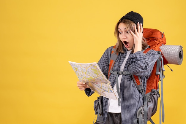 Vista frontal de uma mulher viajante maravilhada com uma mochila, olhando para o mapa
