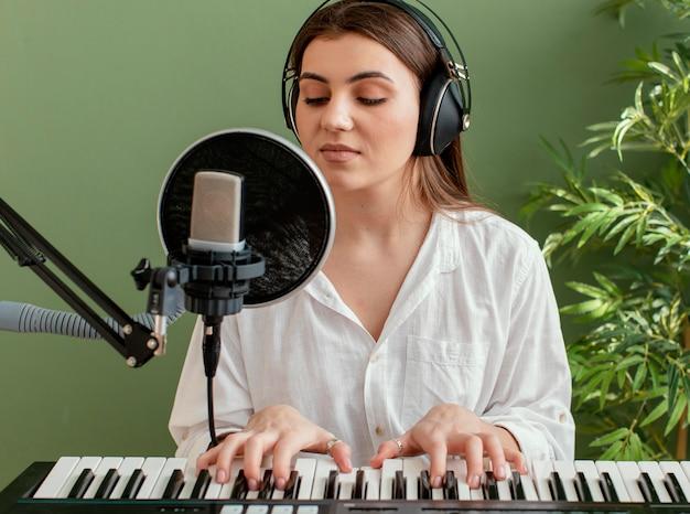 Vista frontal de uma musicista cantando e tocando teclado de piano