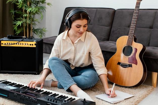 Vista frontal de uma musicista com teclado de piano e violão escrevendo músicas