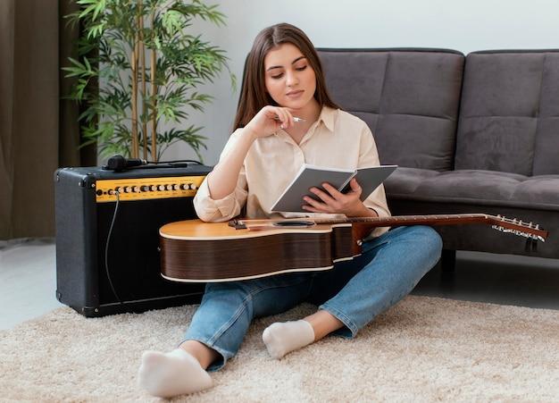 Vista frontal de uma musicista com violão escrevendo canções
