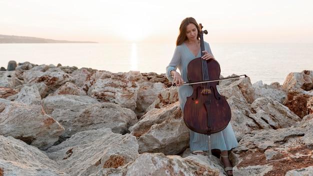 Vista frontal de uma musicista com violoncelo e espaço de cópia