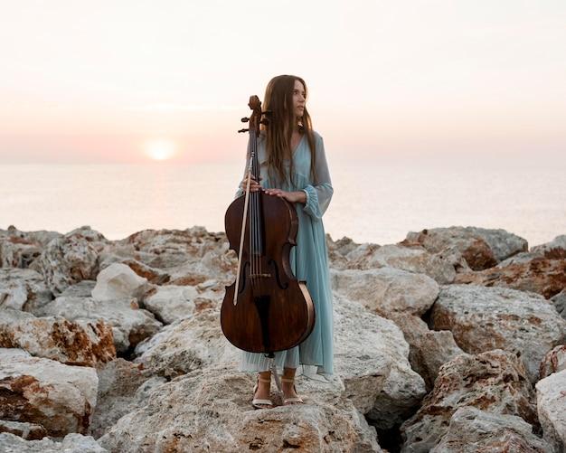 Vista frontal de uma musicista com violoncelo