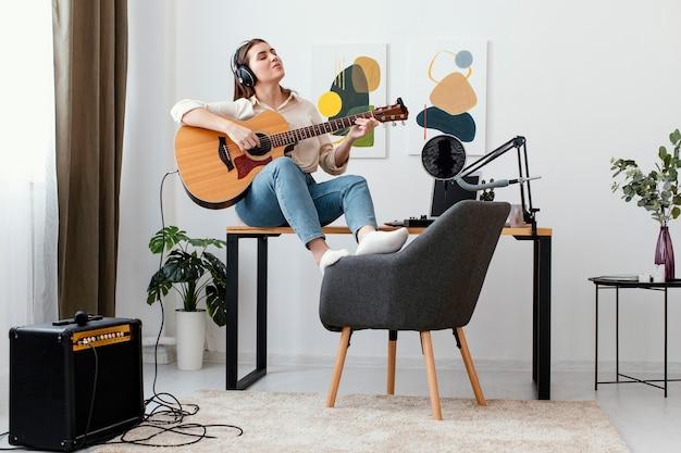 Vista frontal de uma musicista em casa tocando violão e cantando