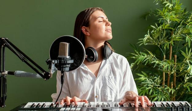 Vista frontal de uma musicista tocando teclado de piano dentro de casa