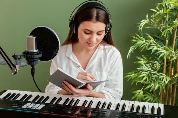 Vista frontal de uma musicista tocando teclado de piano e escrevendo músicas durante a gravação