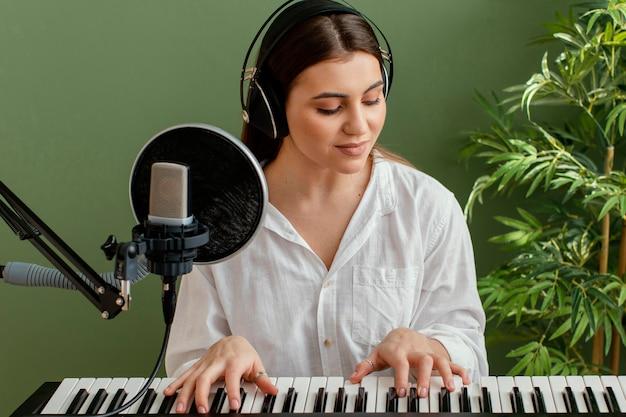 Vista frontal de uma musicista tocando teclado de piano