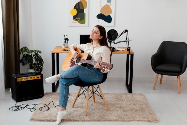 Vista frontal de uma musicista tocando violão em casa