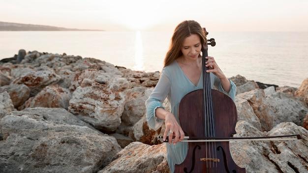 Vista frontal de uma musicista tocando violoncelo ao ar livre