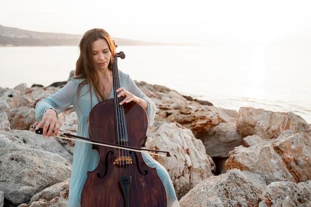 Vista frontal de uma musicista tocando violoncelo com espaço de cópia