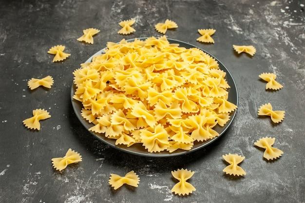 Vista frontal de uma pequena massa crua dentro do prato na massa de farinha cinza-escuro muitas fotos de massas italianas de cor de comida