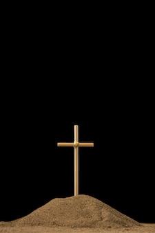 Vista frontal de uma pequena sepultura com uma cruz em preto