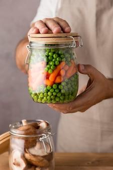 Vista frontal de uma pessoa segurando ervilhas e cenouras em frasco de vidro