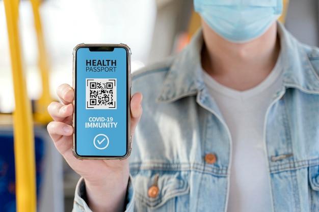 Vista frontal de uma pessoa segurando um passaporte de saúde virtual em um smartphone