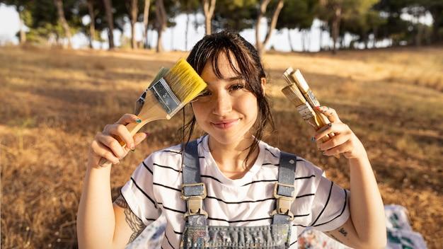 Vista frontal de uma pintora com pincéis
