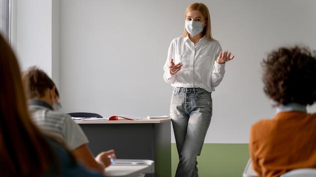 Vista frontal de uma professora com máscara médica ensinando em sala de aula