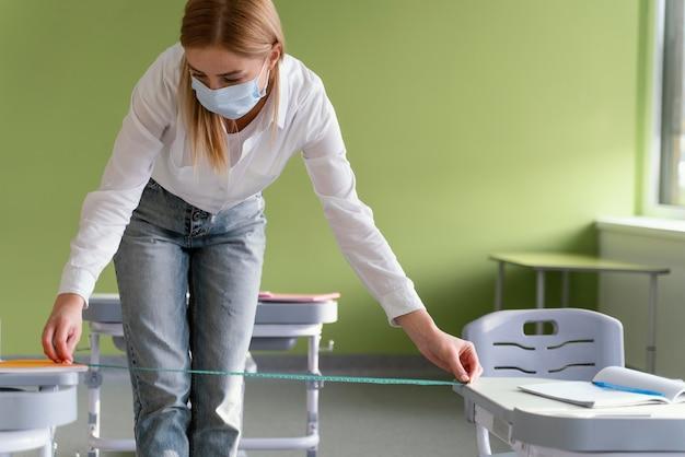 Vista frontal de uma professora com máscara médica medindo a distância entre as bancadas da classe