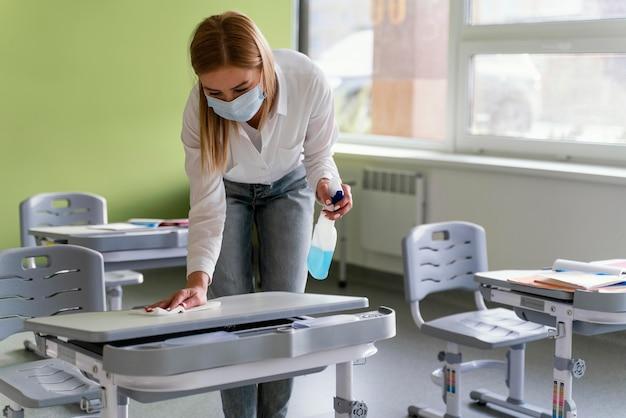 Vista frontal de uma professora desinfetando bancos escolares em sala de aula