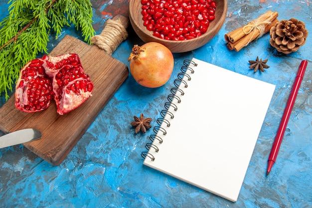 Vista frontal de uma romã cortada e faca de jantar na tábua de cortar sementes de romã em uma tigela e sementes de anis de canela de romã um caderno caneta vermelha sobre fundo azul