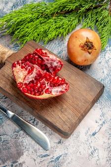 Vista frontal de uma romã cortada em uma faca de mesa de romã em branco-azulado